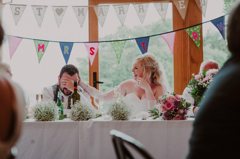 upton barn wedding photography in devon, groom with head in hands during speeches.