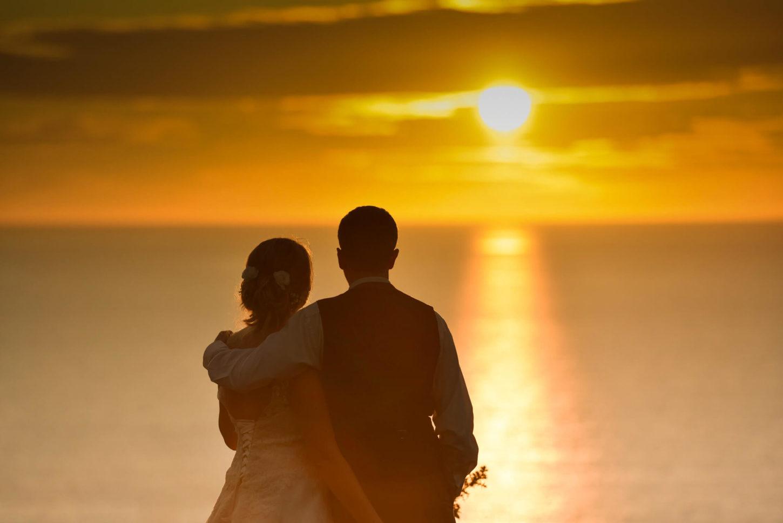 Bride & groom enjoying sunset at ocean Kave westward Ho! Ocean Cave, Devon wedding photographer