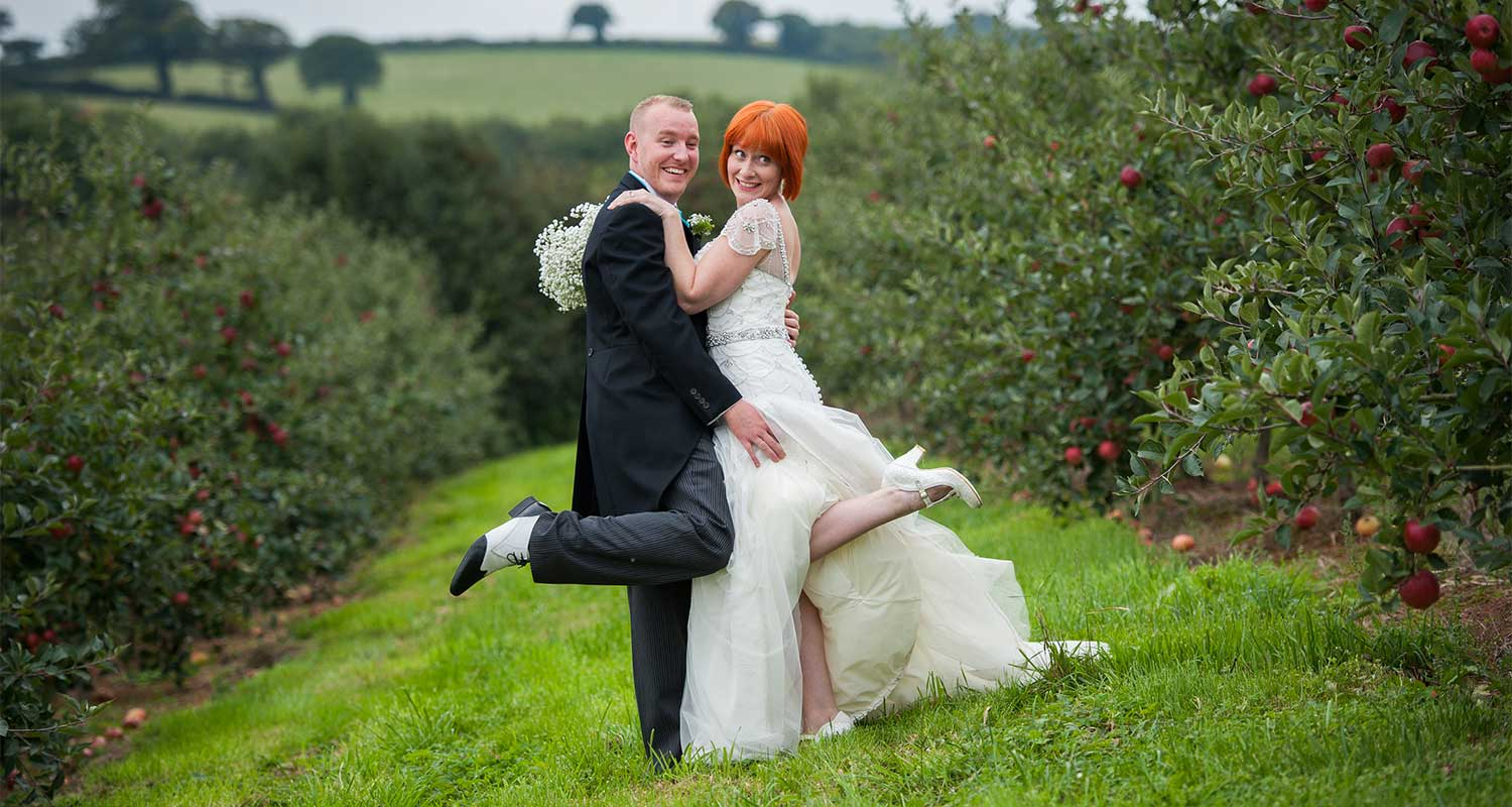 the cornbarn in devon, bride and groom in the orchard at the cornbarn in devon.