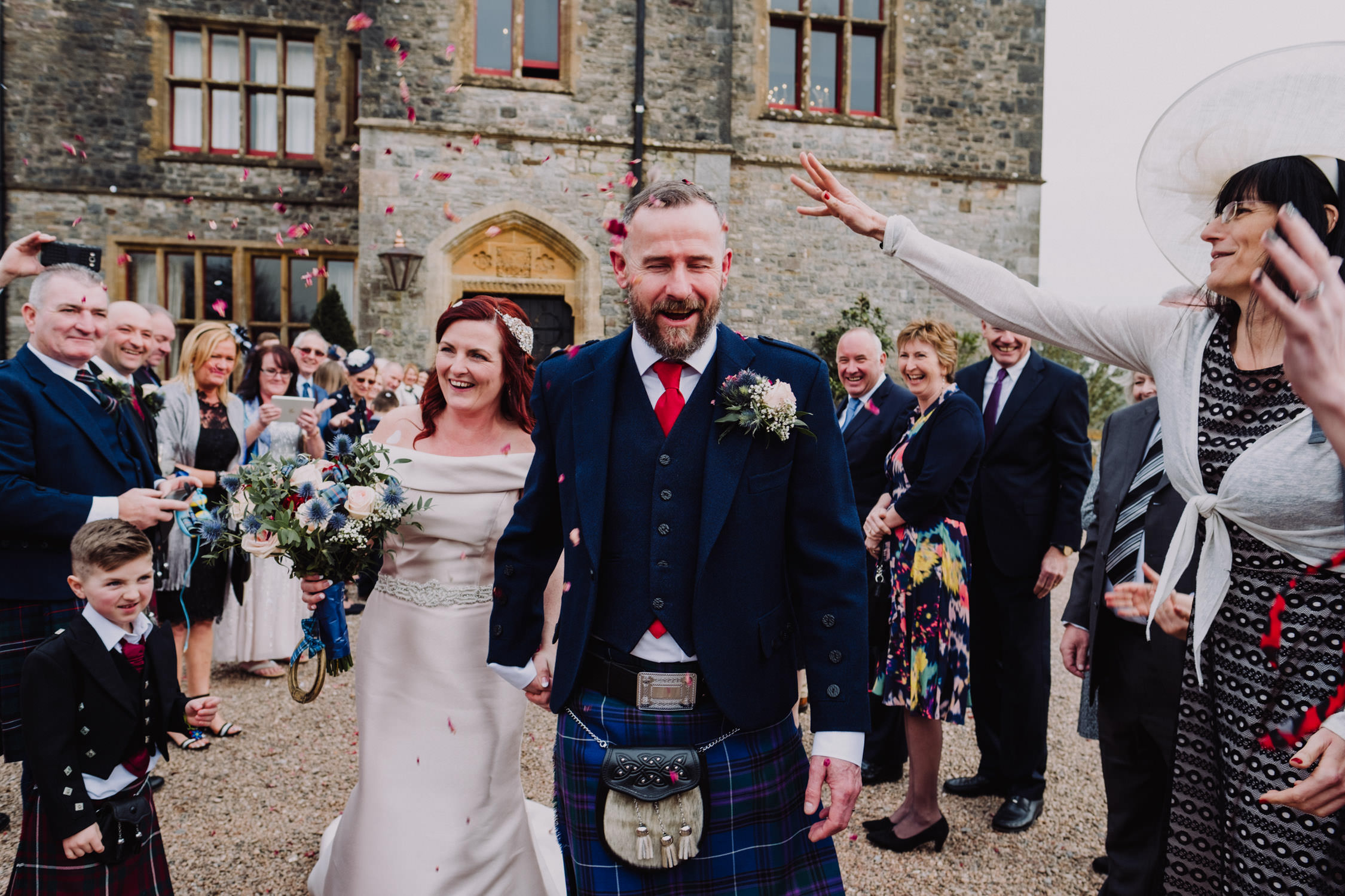 Huntsham court wedding, bride and groom walking through confetti , Devon wedding photographer