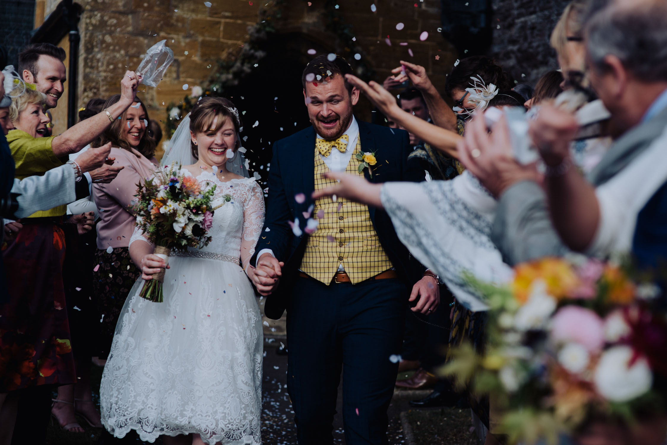 Bride and groom enjoying walking through confetti, somerset wedding photographer