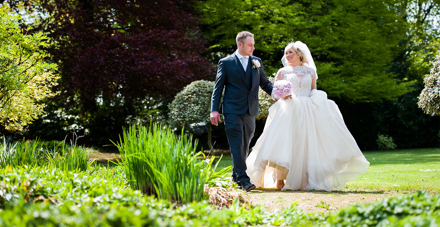 bride and groom walking in summer garden