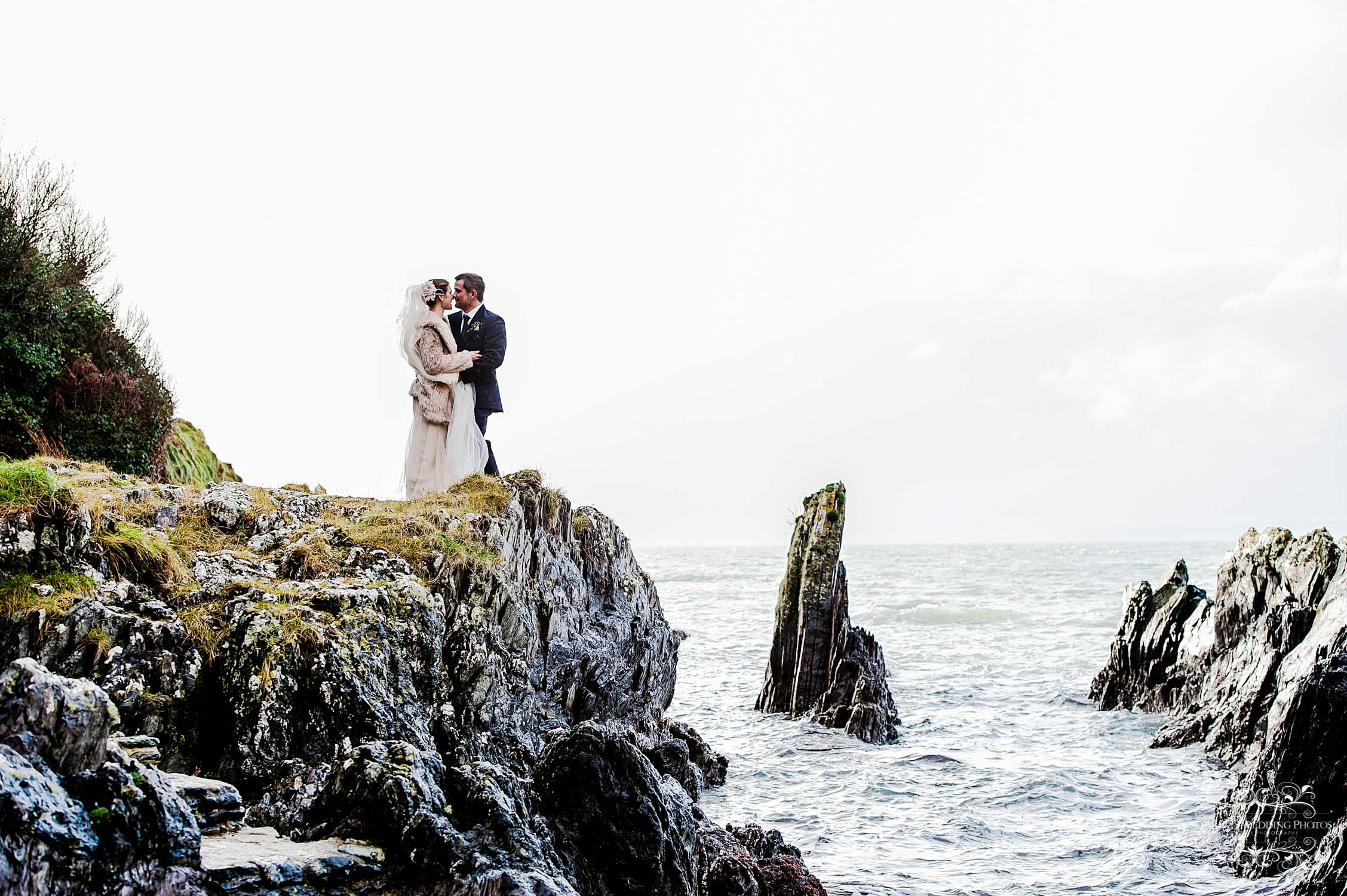 bride and groom on rocks overlooking the sea, polhawn fort cornwall