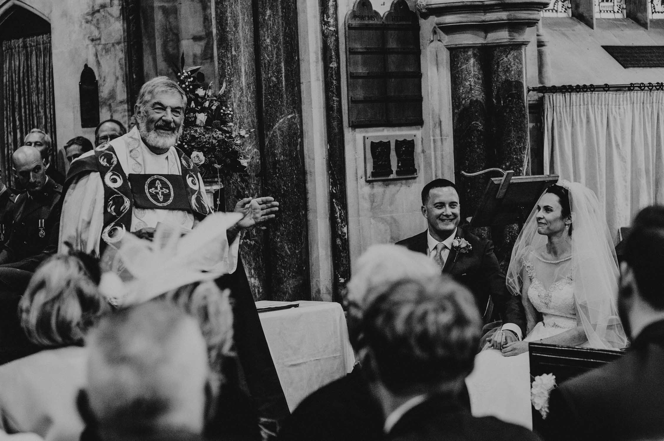 Vicar conducting a wedding with a seated bride and groom at st audries park in somerset, reportage wedding photographer in somerset.