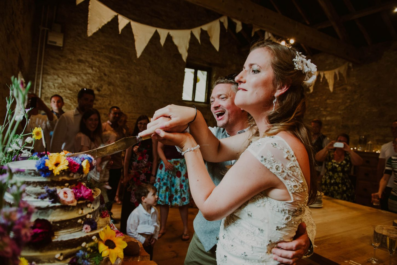 somerset wedding photographer capturing bride and groom cutting the cake, streamcombe farm wedding