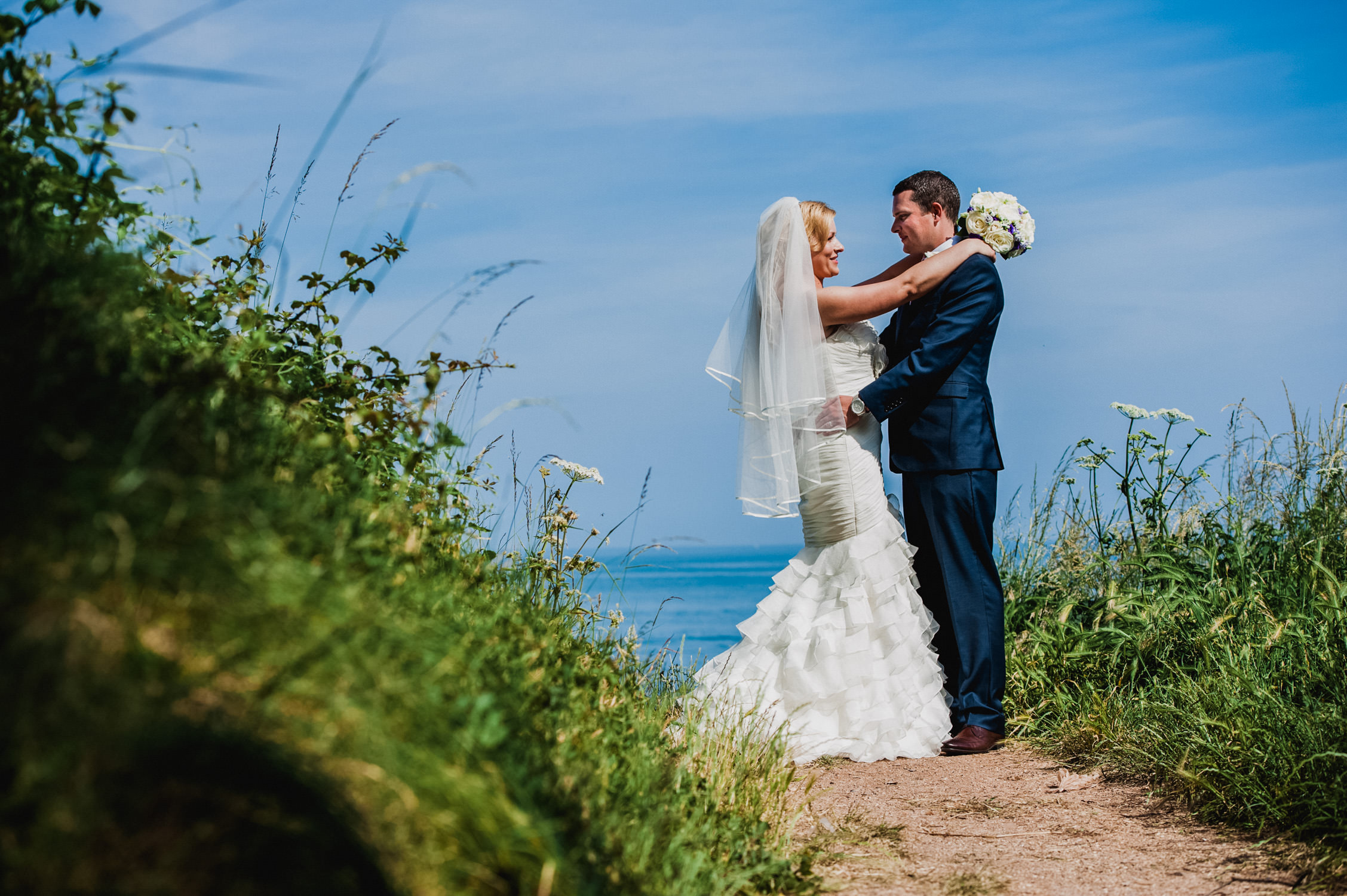 bride and groom standing on the beach, wedding photography devon