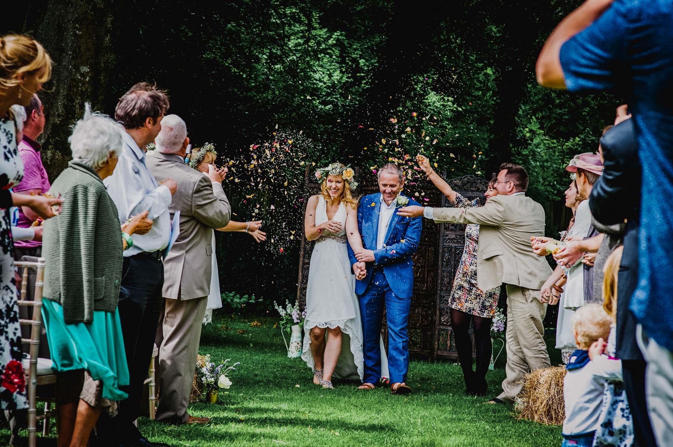 Devon wedding photography, bride and groom walking through confetti, outside wedding in devon, woodland humanist wedding, zena birch wedding, wedding photographer devon