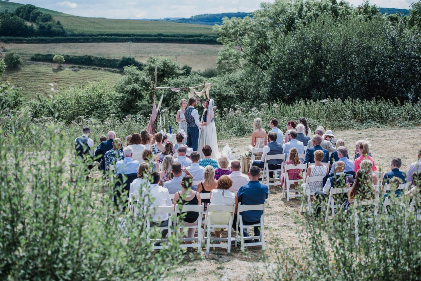whitemoor wedding photographer north devon, humanist wedding in the north devon countryside with guests seated watching the ceremony unfold